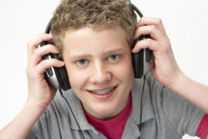 A smiling teenage boy with braces, wearing headphones.